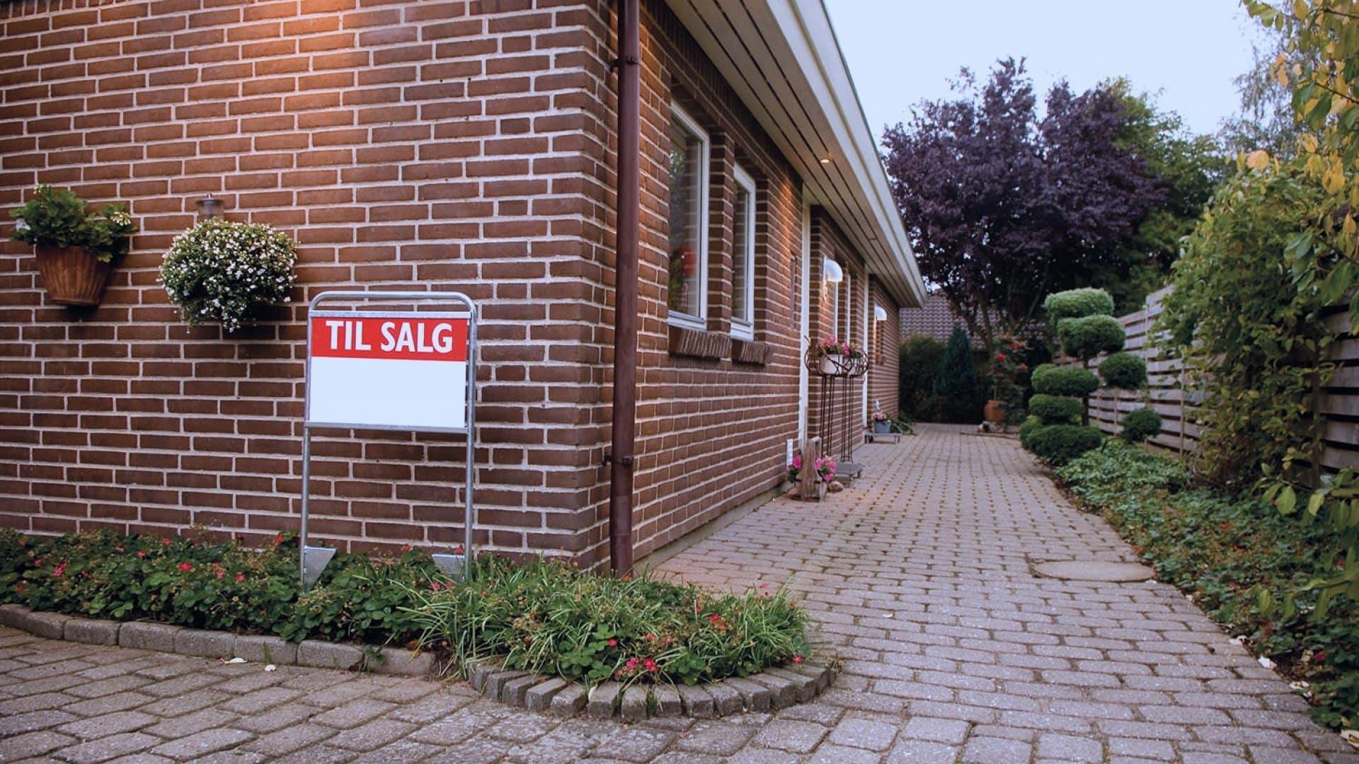 """Et hus med et """"til salg"""" skilt foran"""