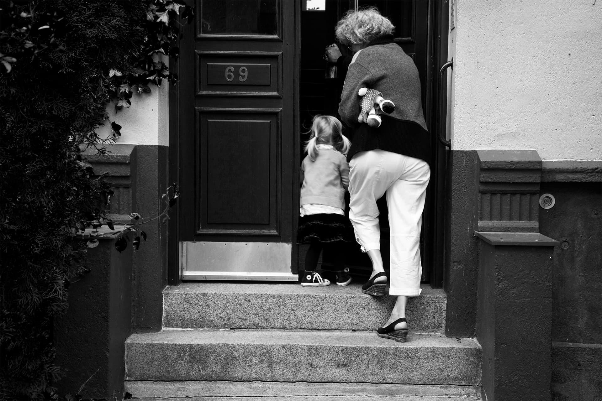 Kvinde og barn på trapperne til deres nye hjem.